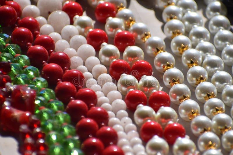Ожерелья жемчуга ожерелья жемчуга ожерелье жемчуга белого красное стоковое изображение