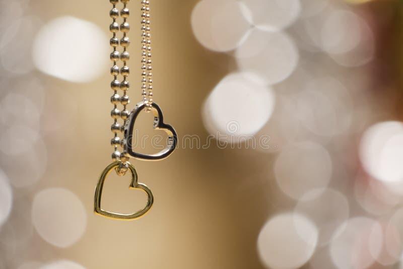 2 ожерелья шкентелей сердец изолированного в нежности запачкали накаляя предпосылку стоковая фотография