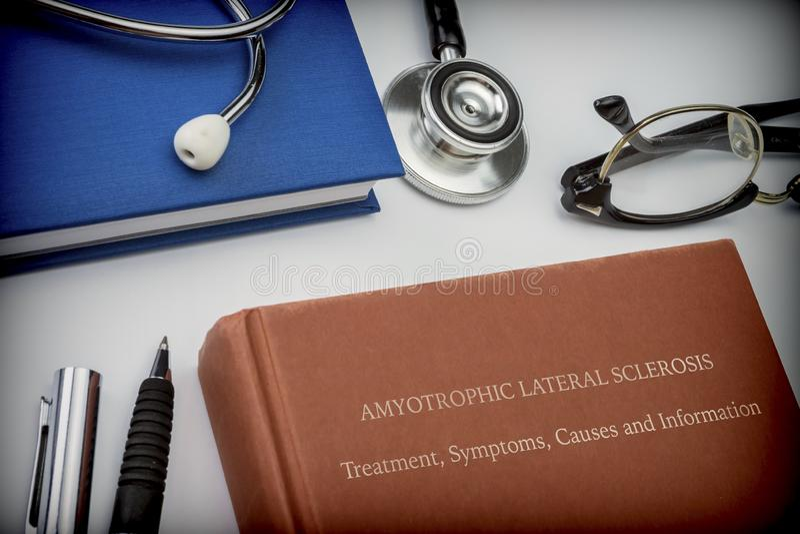Озаглавленный боковой амиотрофический склероз книги вместе с медицинским оборудованием стоковые фото