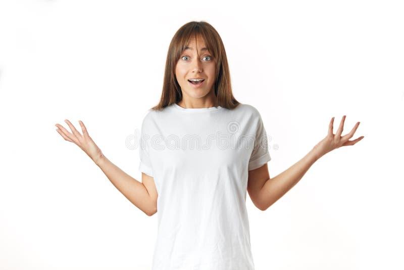 Озадаченная положительная девушка показывая вытаращиться ладоней изолированный над белой предпосылкой стоковые изображения rf