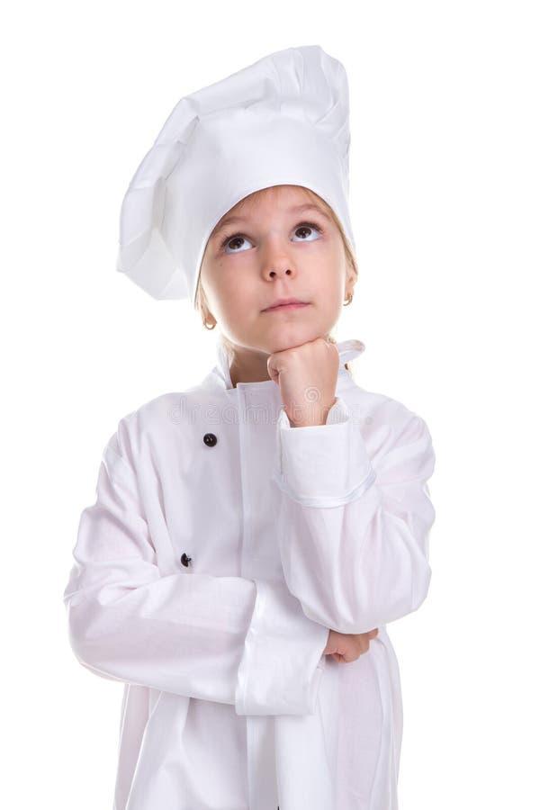 Озадаченная форма серьезного шеф-повара девушки белая изолированная на белой предпосылке, смотрящ вверх, держа кулак под подбород стоковое изображение rf