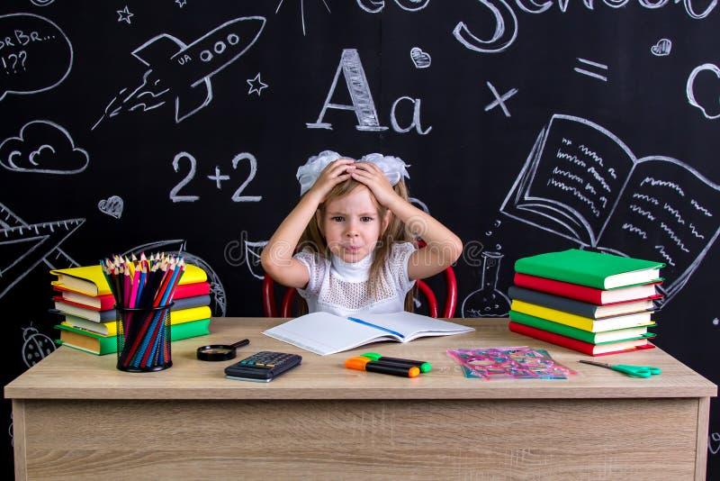 Озадаченная школьница сидя на столе с книгами, школьными принадлежностями, держа ее обе руки над головой стоковое фото rf
