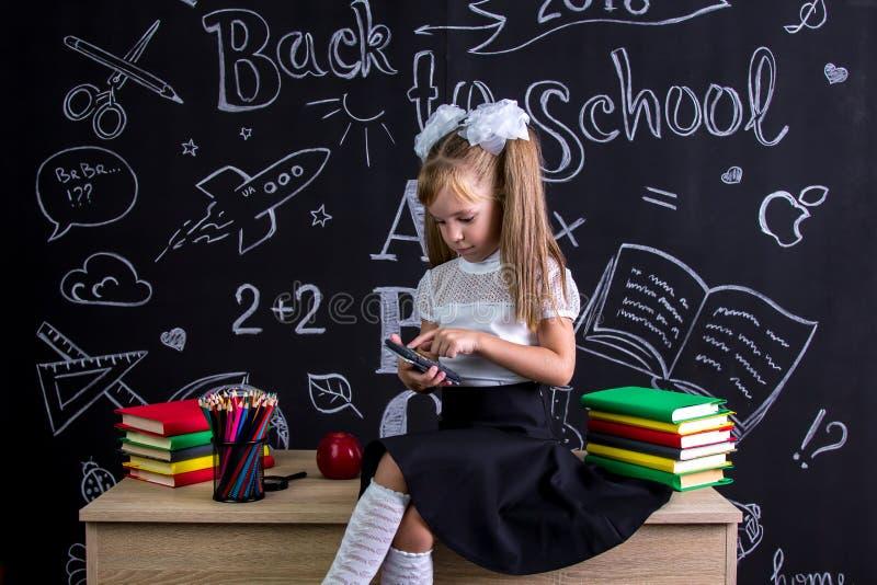 Озадаченная школьница сидя на столе с книгами, школьными принадлежностями, делая математики с калькулятором стоковые изображения