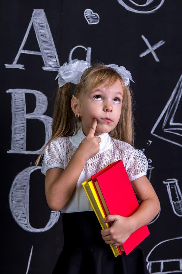 Озадаченная школьница стоя перед доской как предпосылка при несколько книги держа их и указывать стоковая фотография