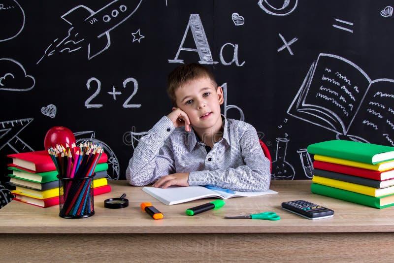 Озадаченный превосходный школьник сидя на столе с книгами, школьными принадлежностями, при одна рука положенная под cheeck стоковые изображения