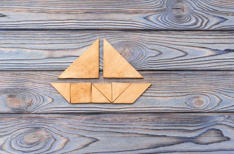 Озадачьте в форме шлюпки на деревянной предпосылке стоковое фото rf