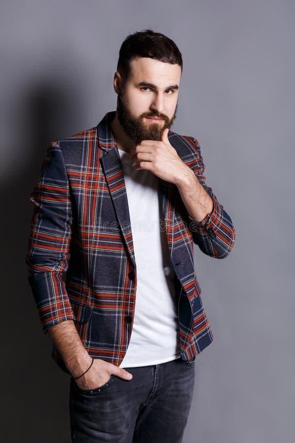 Озадаченный молодой человек штрихуя бороду смотря камеру стоковые изображения rf