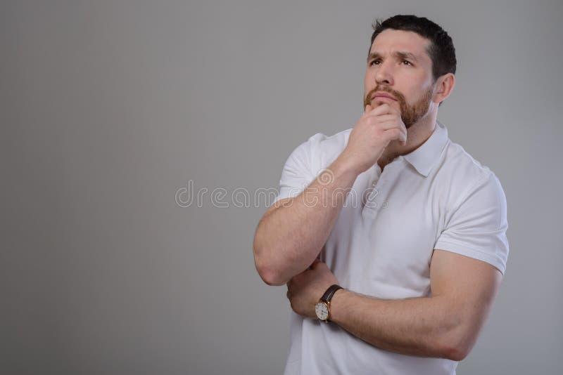 Озадаченный молодой человек штрихуя касающую бороду смотря камеру над серой предпосылкой стоковое фото rf