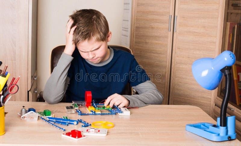 Озадаченный предназначенный для подростков мальчик делая проект школы электронный в его комнате на стоковое фото