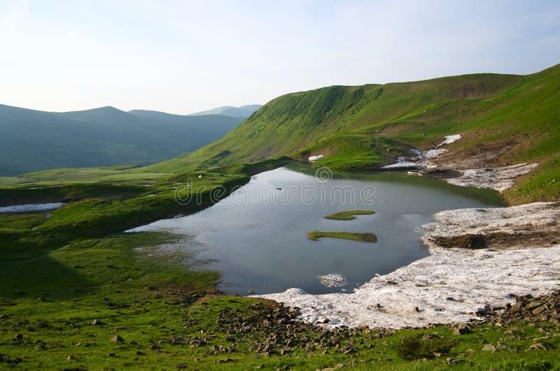 Озеро высокой горы высокогорное и панорамный сценарный взгляд к горной цепи стоковое изображение
