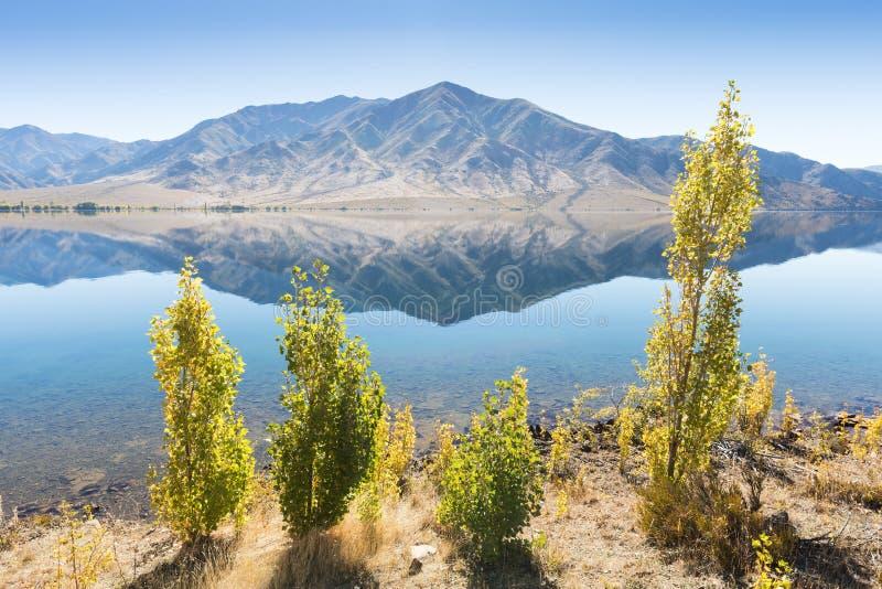 Озеро в сухом ландшафте с деревьями и горами Горизонтальное изображение с отражениями в воде Красивая предпосылка стоковая фотография rf
