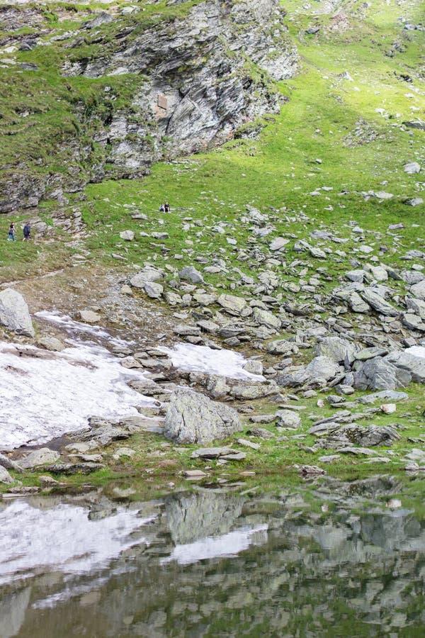 Озеро гор около берега с зелеными холмами стоковые изображения