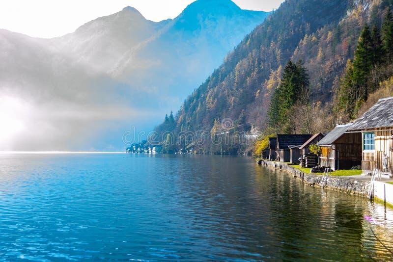 Озеро гор окруженное скалистыми горами покрытыми с соснами, деревянными домами стоковые изображения rf