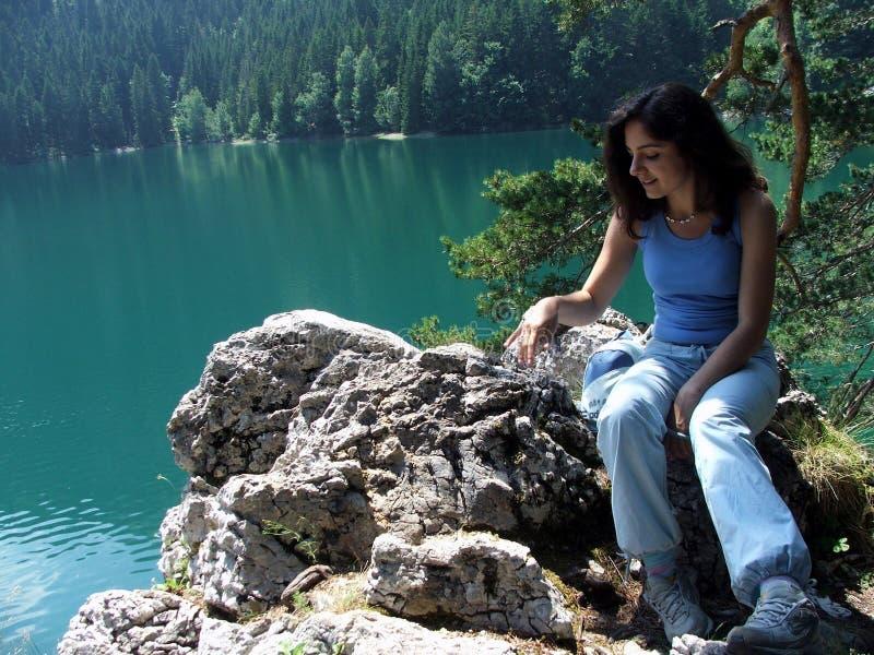 озеро девушки около сидеть утесов стоковые фото