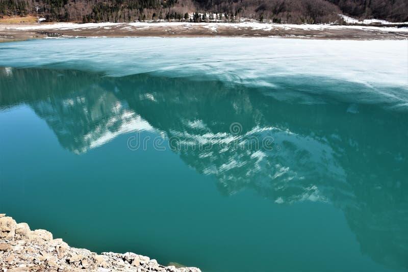 Озеро Кленталерзе по-прежнему частично покрыто льдом и отражает панораму Альп стоковое изображение rf