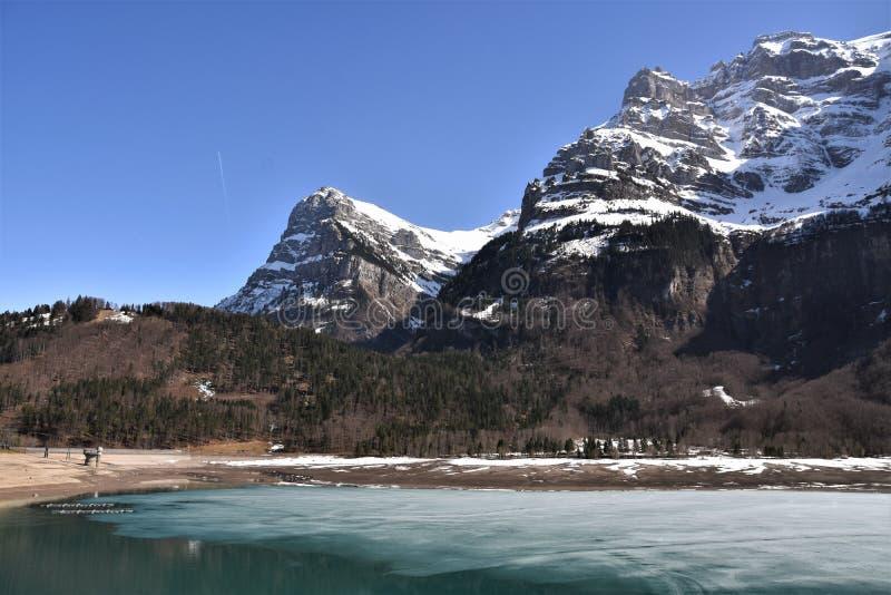 Озеро Кленталерзе по-прежнему частично покрыто льдом и панорамой Альп стоковые фото