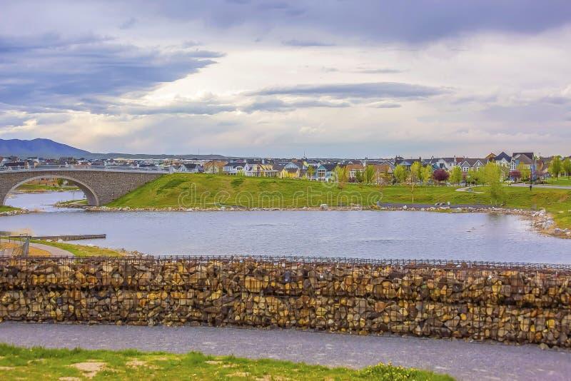 Озеро с банком каменного и сдобренного моста под небом заполненным с облаками стоковое фото rf