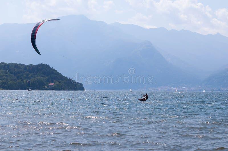 Озеро Como, Италия - 21-ое июля 2019 Водные виды спорта: kitesurfer занимаясь серфингом ветер на волнах на яркий солнечный летний стоковое изображение