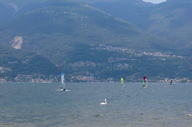 Озеро Como, Италия - 21-ое июля 2019 Водные виды спорта: windsurfers и kitesurfers занимаясь серфингом ветер на волнах на солнечн стоковое фото