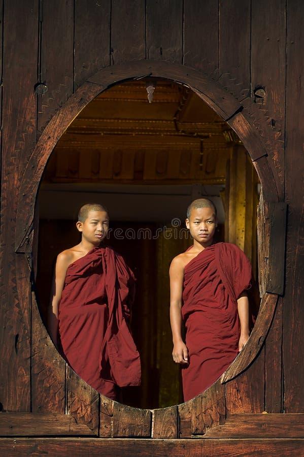 ОЗЕРО INLE, МЬЯНМА - 18-ое ноября: Неопознанные молодые монахи смотрят из окна монастыря от монастыря Shwe Yaunghwe в Nyaun стоковые фотографии rf