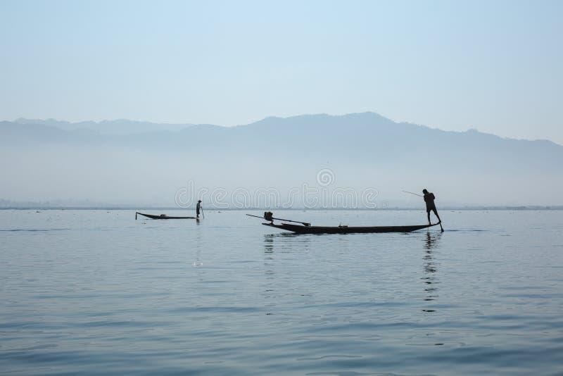 Озеро Inle, Мьянма - 25-ое февраля 2014: Рыболов гребя его шлюпку дальше стоковое фото