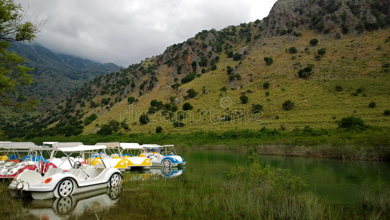 Озеро Kournas посреди blossoming весны и большое количество катамаранов в форме машин стоковое фото