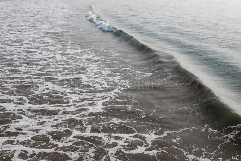 Океанская волна и цаца причаливая от права в утре стоковые изображения rf