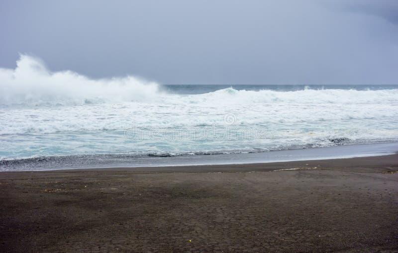 Океанские волны разбивая на влажном пляже под темными облаками стоковое фото