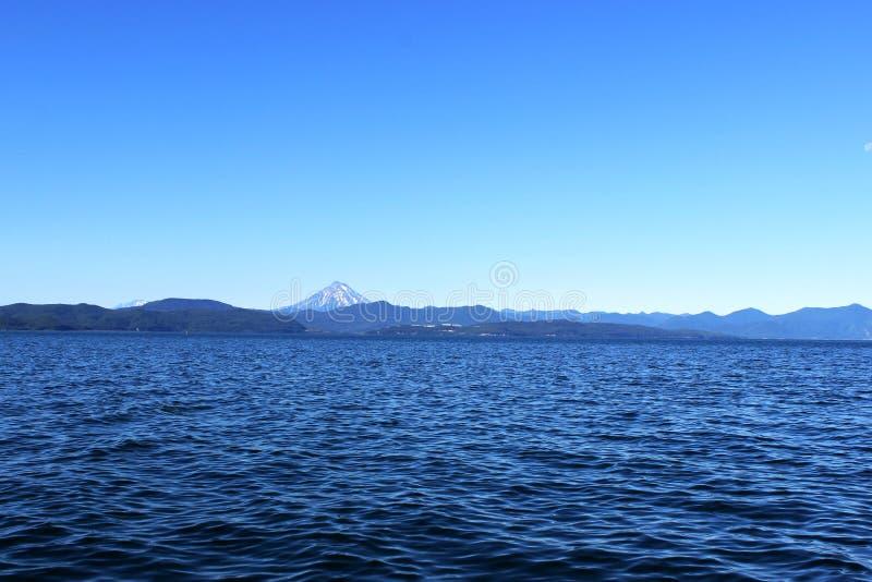 Океанские волны с вулканом на горизонте стоковое изображение