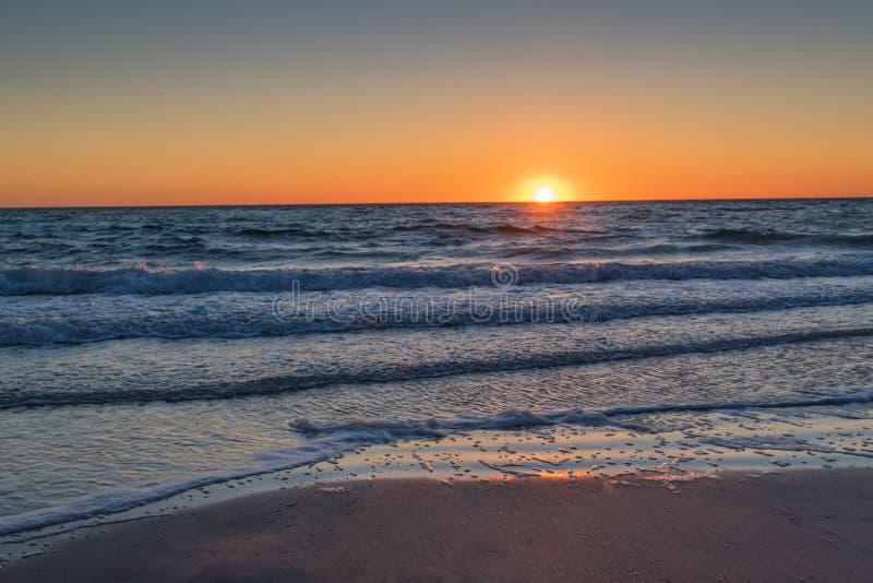Океан и солнце песка на заходе солнца стоковые изображения rf
