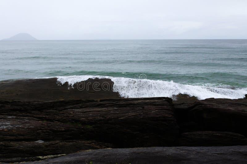 Океан с волнами разбивая в камнях стоковое изображение