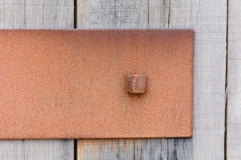 Окисленная металлическая пластина прикрепленная к деревянной загородке стоковые фото