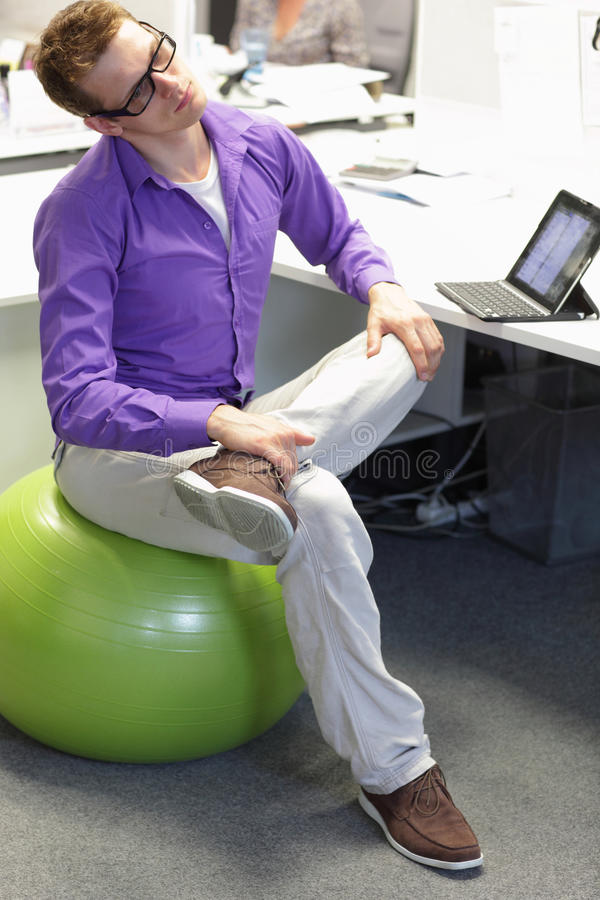 Оккупационная борьба болезнями - человек на шарике стабильности имея пролом для тренировки стоковые фотографии rf