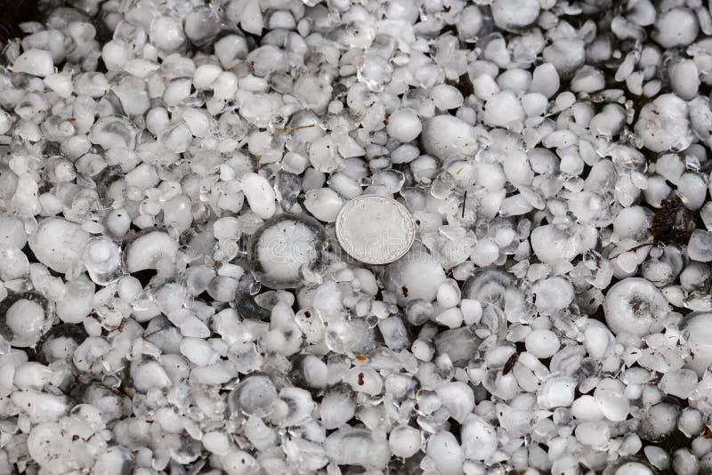 Оклик определенный размер с более большой монеткой, градины на том основании после hailstorm стоковые изображения