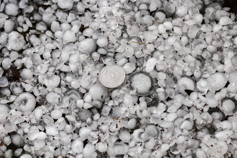 Оклик определенный размер с более большой монеткой, градины на том основании после hailstorm, оклика большого размера стоковое изображение