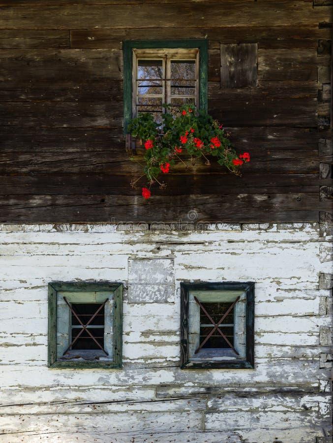 3 3 окна, исторический сельский дом в горных вершинах с красным flo стоковое фото