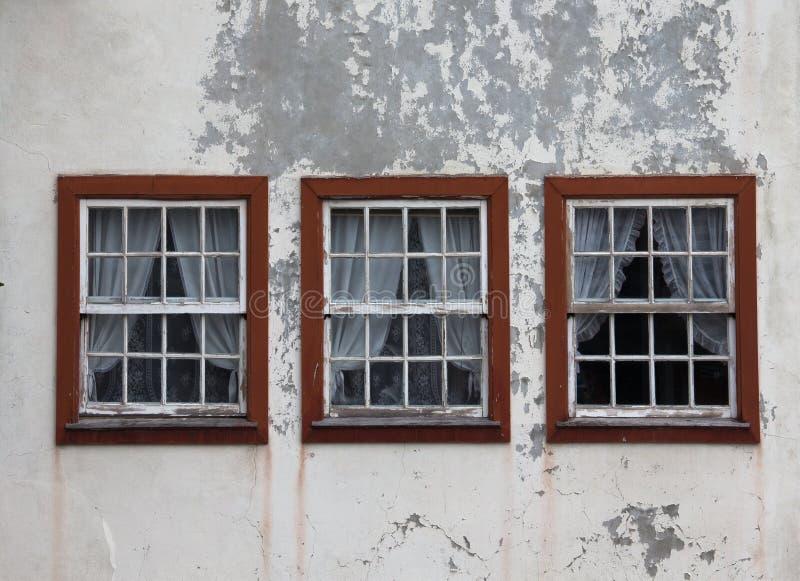 3 окна на затрапезной стене закрыли с занавесами стоковое фото