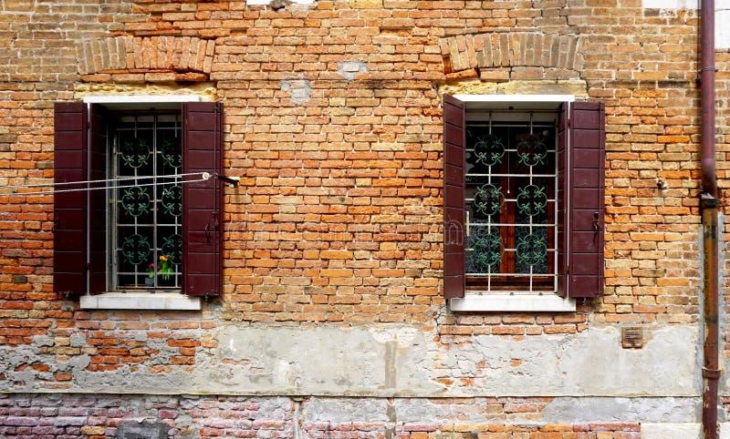 2 окна с зданием стены спада кирпича стоковое фото
