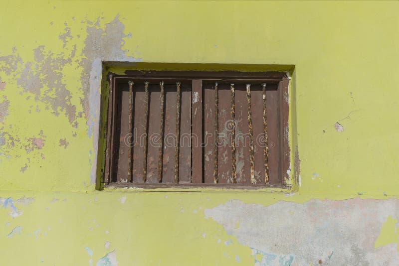 Окно в старой, затрапезной, желтой стене, с закрытыми шторками и за старым, ржавым грилем стоковые изображения rf
