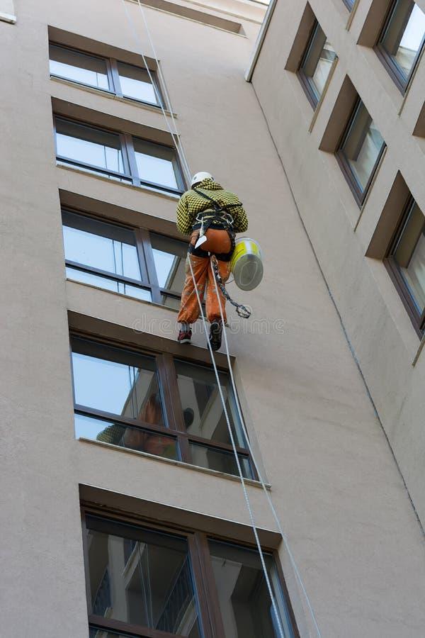 Окно зеркала чистки человека на высоком здании подъема Альпинист на работе как профессиональный уборщик окон стоковые изображения rf