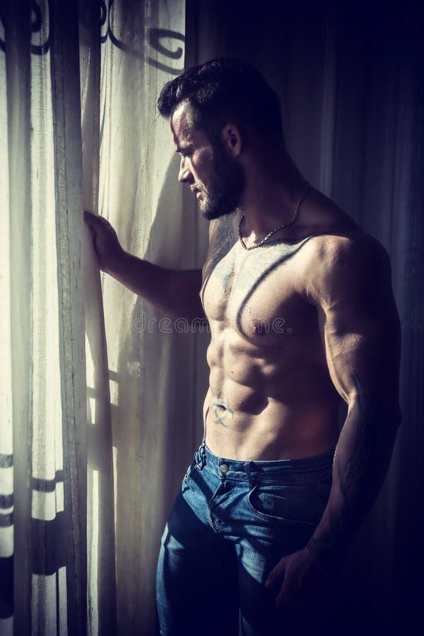 Окно мышечного топлесс человека готовя стоковое изображение