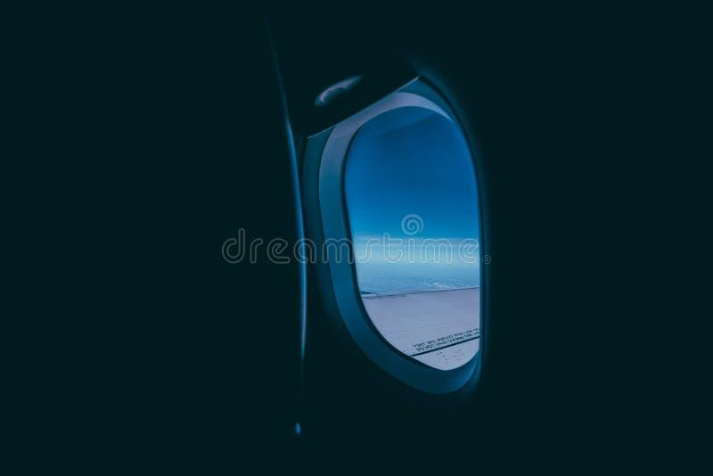 Окно самолета с взглядом крыла и голубого неба стоковые фото
