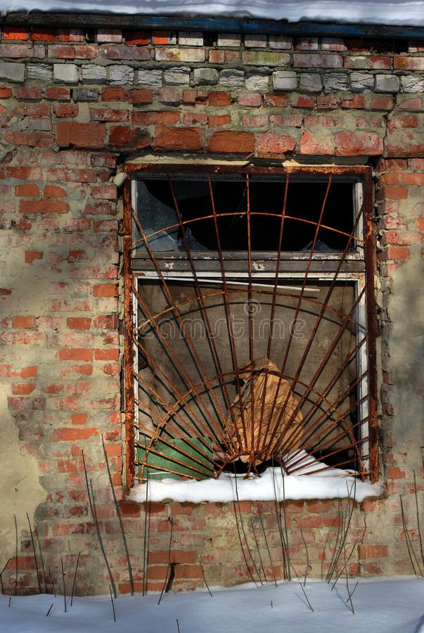 Окно старого кирпичного здания покрытого с ржавым утюжит решетку, улицу зимы, предпосылку grunge стоковые изображения rf