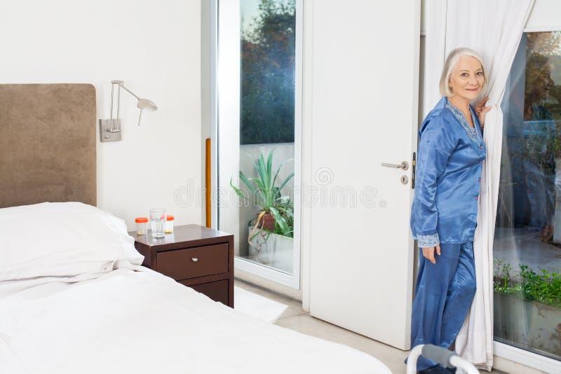 Окно старшей женщины готовя на доме престарелых стоковое фото rf