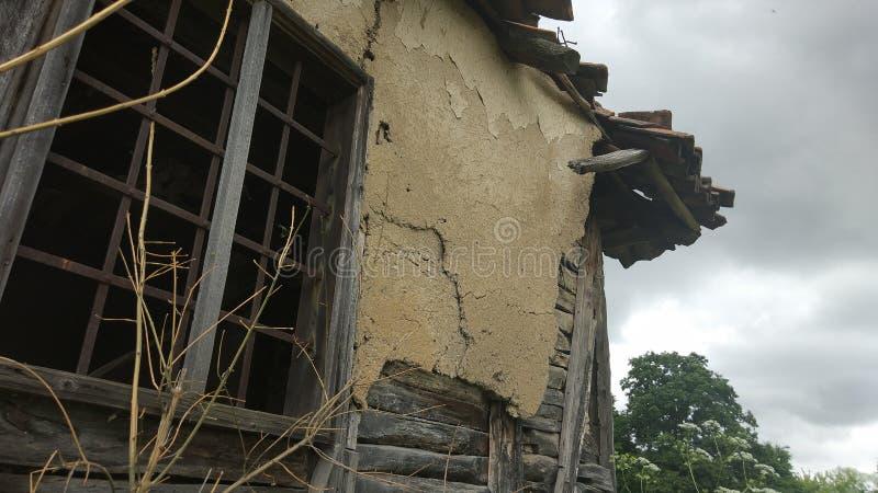 Окно с барами и стена старых получившихся отказ хижин в горе стоковые изображения