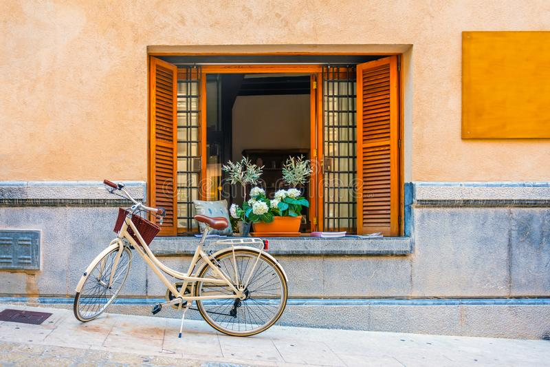 Окно с коричневыми деревянными шторками, книгами и вазами Велосипед под окном стоковая фотография rf