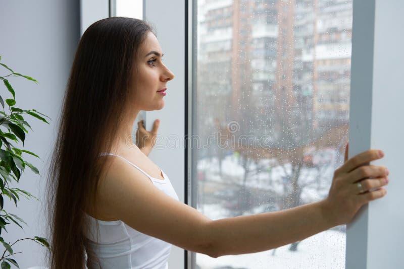 около женщины окна Мечта и ослабляет стоковая фотография rf