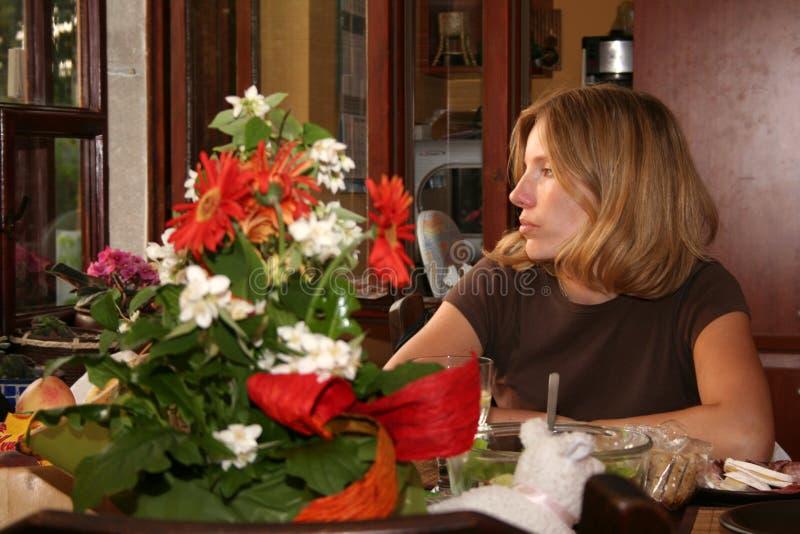 около унылой женщины окна стоковая фотография rf