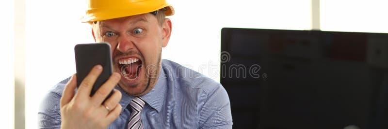 Окрик сердитого архитектора дизайнерский, который нужно позвонить по телефону в руке стоковые фотографии rf
