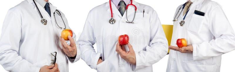 3 доктора нося стетоскопы держа сочные яблока стоковые изображения rf